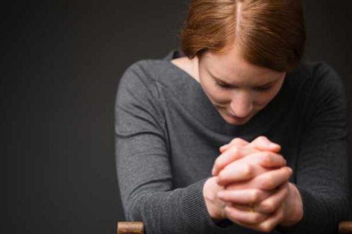 woman praying during prelude